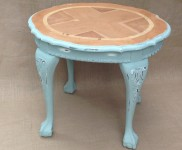An occasional table with natural wood top and ball and claw feet