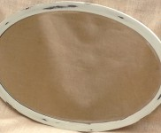 An oval mirror with bevelled edge,painted in colour linen, perfect for any hall way